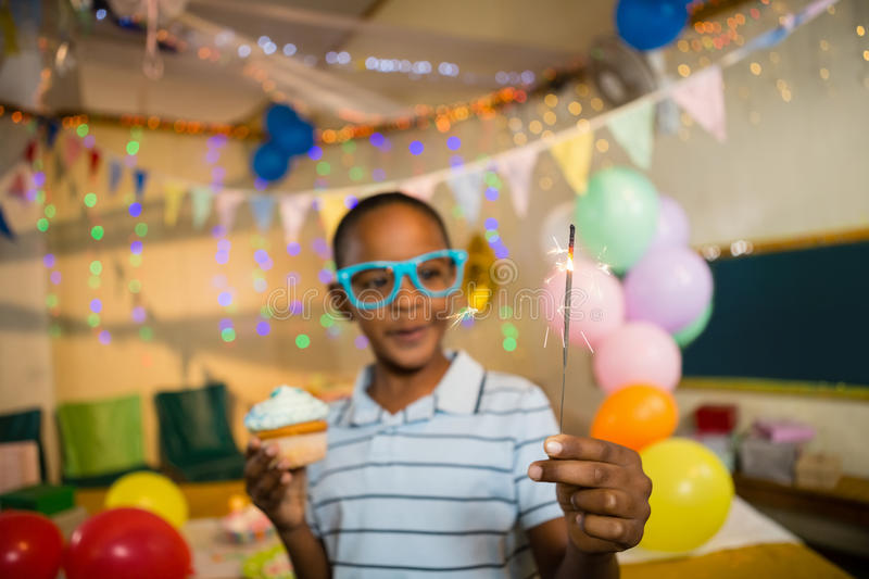 Cute boy holding sparkler and cupcake during birthday party. At home stock images
