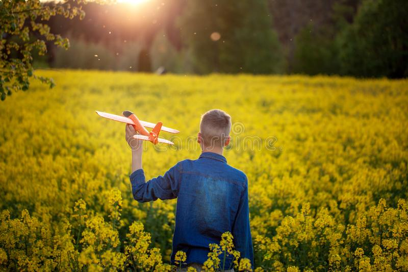 Cute Boy holds toy plane in his hand on sunset in summer day. Back view stock photos