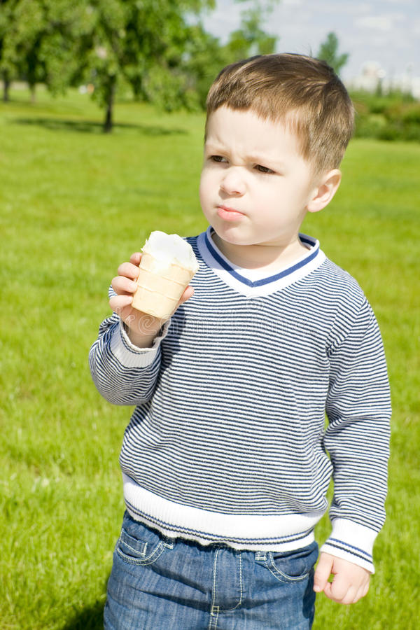 Cute boy with ice-cream. In summer park royalty free stock photography