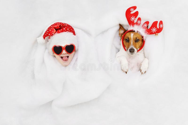 Cute boy and jack russell dog in a reindeer and Santa hat lying. In snow background. Christmas, new year holiday concept royalty free stock photos
