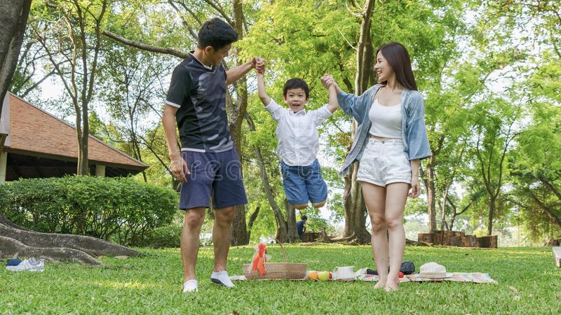 Cute boy jump and hold the hand mother and father in park. royalty free stock photos
