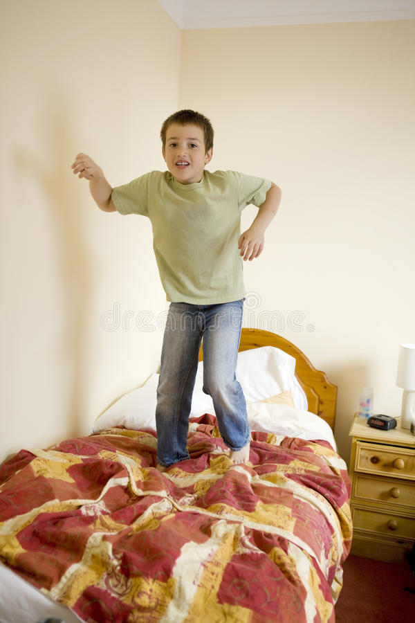 Download Cute Boy Is Jumping On Bed Stock Photo. Image Of Play   12693332