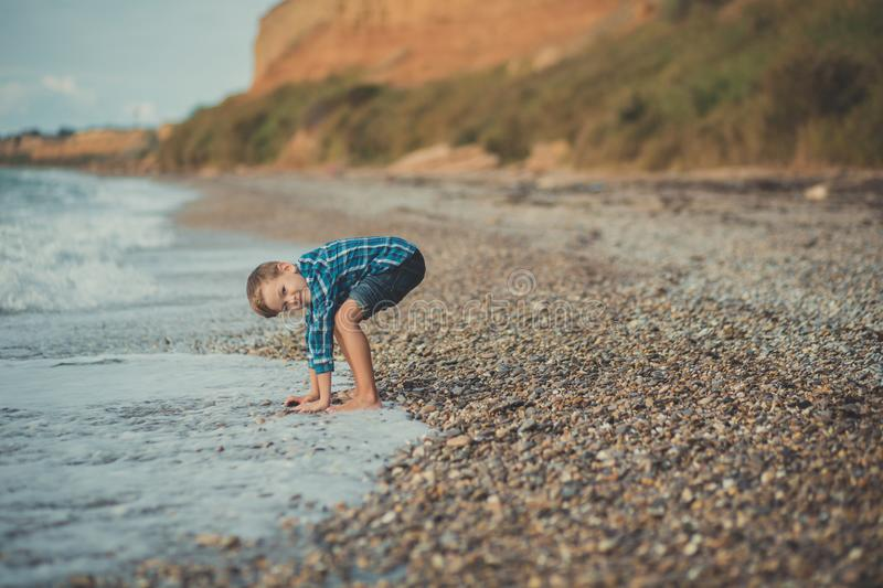 Cute boy kid child wearing stylish shirt and blue jeans barefoot posing running on stone beach with gorgeous ocean sea landscape s royalty free stock photos