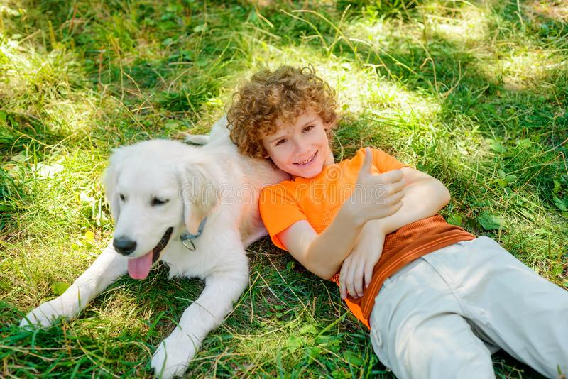 Cute boy lies on his dog. With spread smile and shows OK gesture to reflect his mood. One day from the happy childhood royalty free stock photos