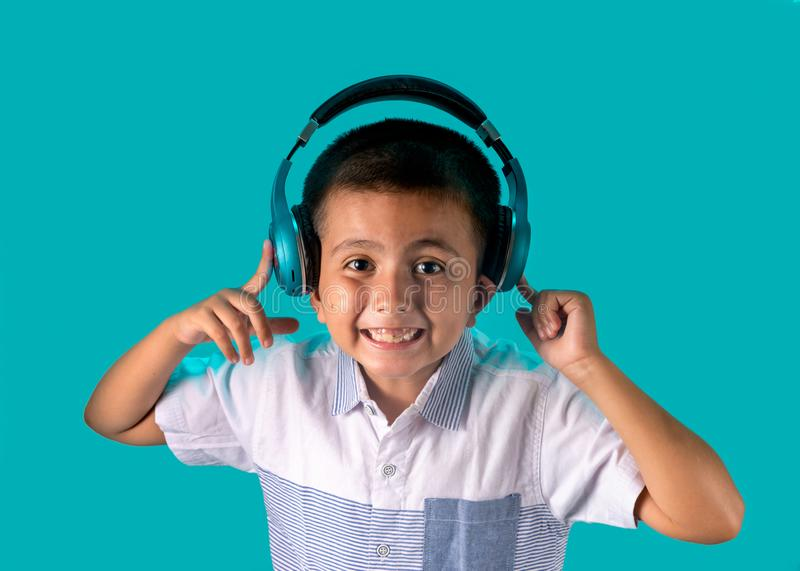 Cute boy listening to music on headphones with exaggerated expressive happy face stock photo