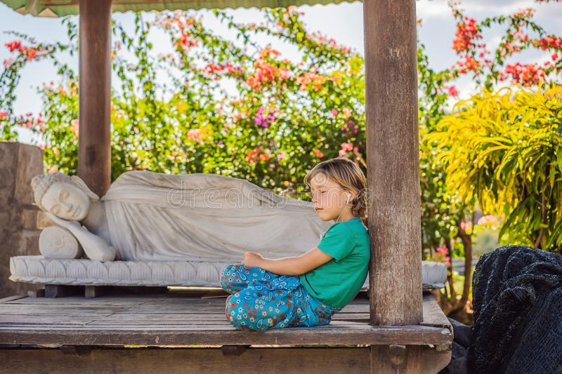 Cute boy listens to music in a Buddhist temple.  royalty free stock photography