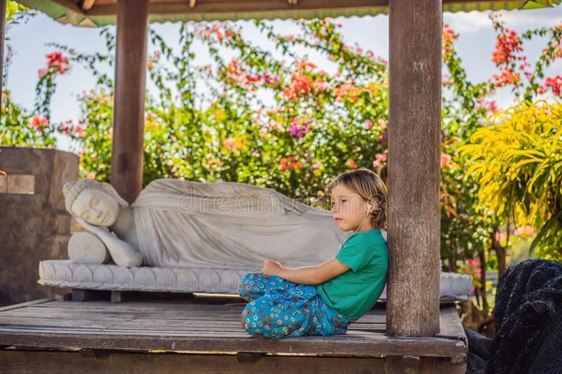 Cute boy listens to music in a Buddhist temple.  stock images