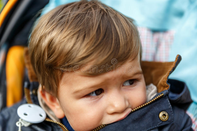 A cute boy looks scared to the side. A cute little boy sitting in a baby chair looks scared to the side stock images