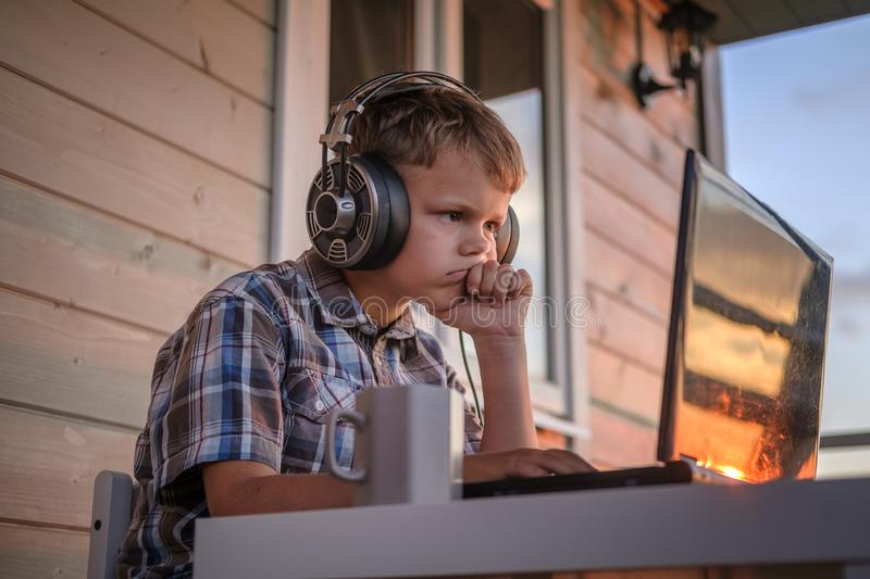Cute boy looks thoughtfully at the monitor screen royalty free stock image