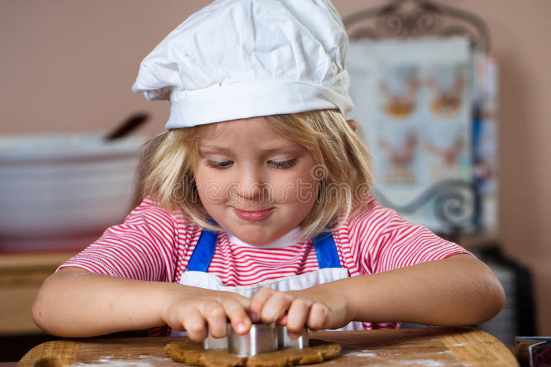 Cute boy making gingerbread man stock photo