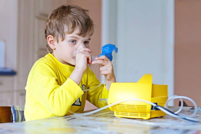 Cute kid boy making inhalation therapy by the mask of inhaler stock images