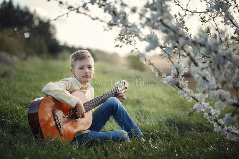Cute boy making music playing the guitar on nature. royalty free stock image