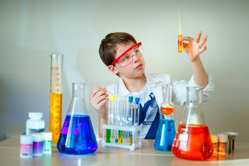 Cute boy is making science experiments in a laboratory. Education royalty free stock images