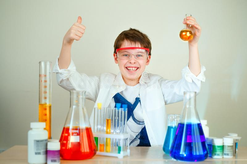 Cute boy is making science experiments in a laboratory. Education royalty free stock image