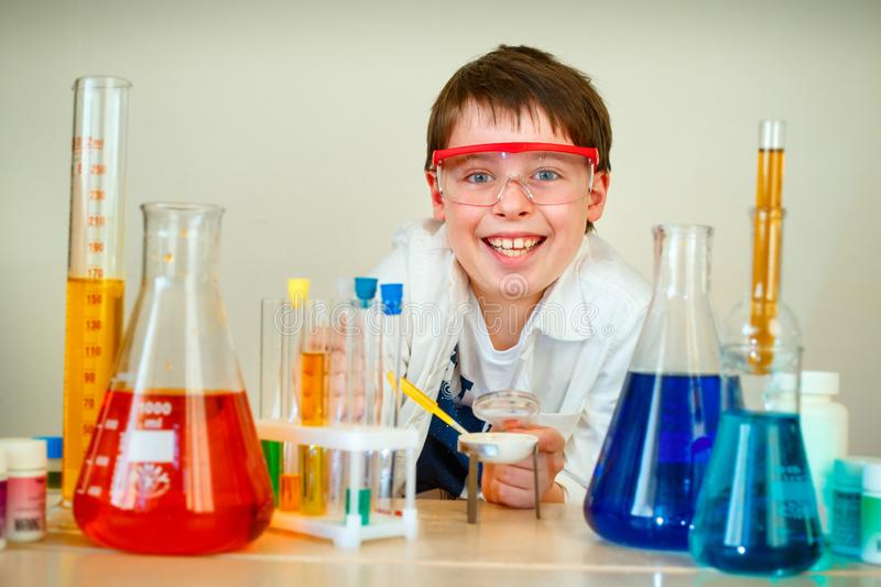 Cute boy is making science experiments in a laboratory stock photography