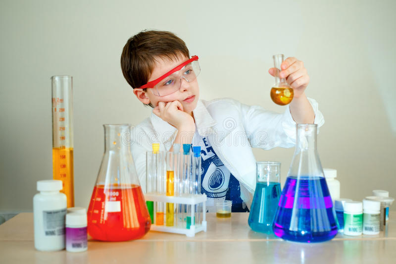 Cute boy is making science experiments in a laboratory royalty free stock images