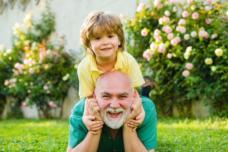Cute boy met vader die buiten speelt Fijne familie Grandson knuffelt zijn opa op vakantie Fijne grootvader en kleinzoon stock fotografie