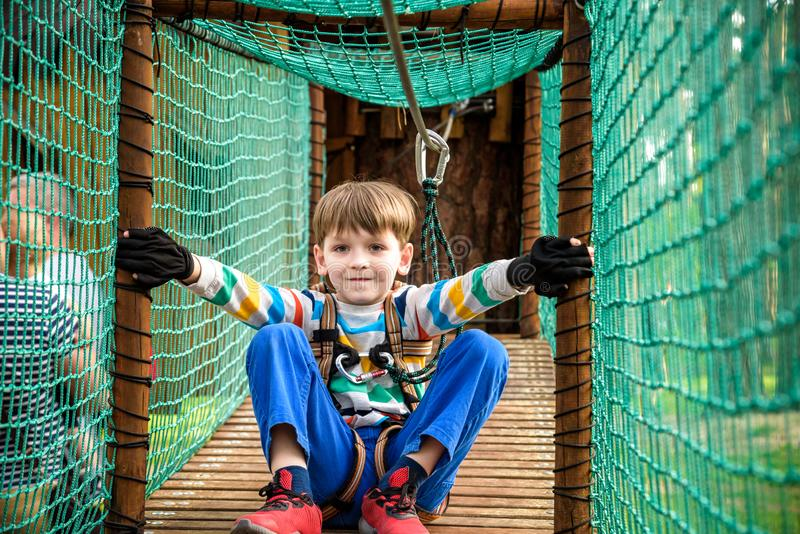 Cute boy overcomes obstacles in rope adventure park. Summer holidays concept. Happy kid playing at rope adventure park. Amusement royalty free stock image