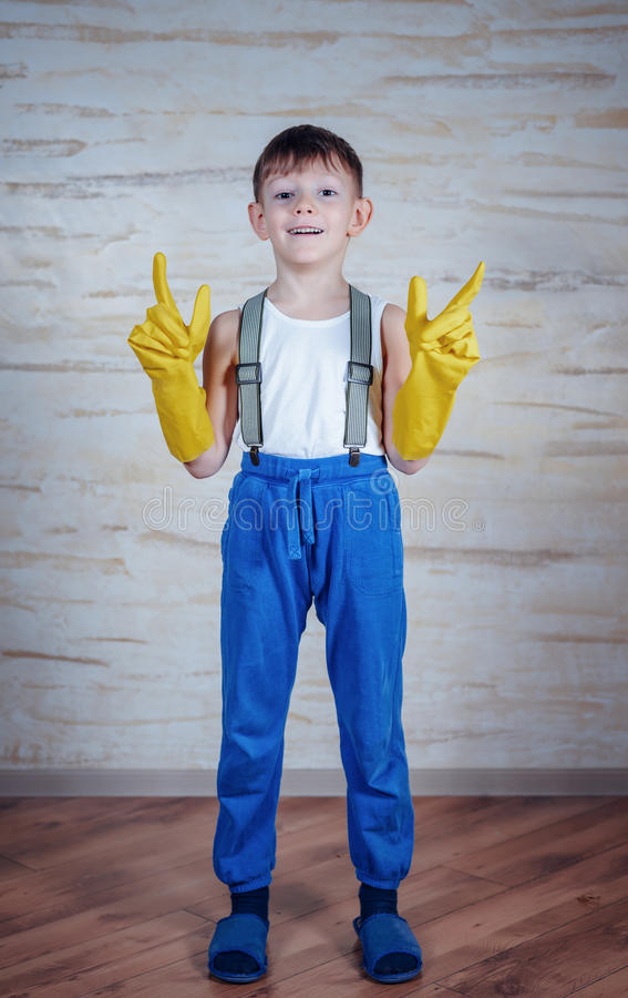 Cute boy in oversized rubber gloves royalty free stock photography