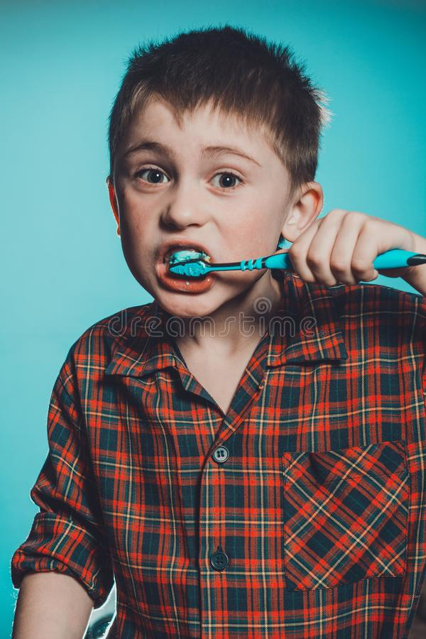 A cute boy in a pajamas brushes teeth with toothpaste before bedtime on a blue background stock image