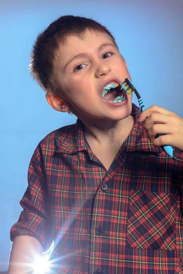 A cute boy in a pajamas brushes teeth with toothpaste before bedtime on a blue background stock photography