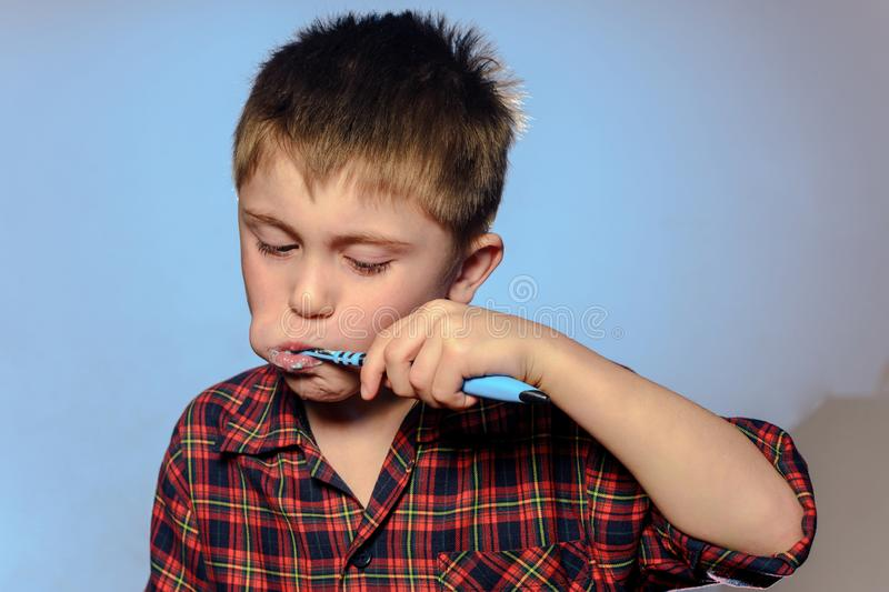 A cute boy in a pajamas brushes teeth with toothpaste before bedtime on a blue background stock photo