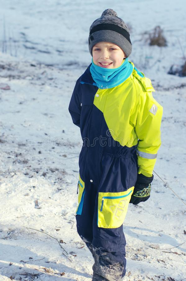 Cute boy play outdoors in snow. Happy boysl playing on a winter walk in nature royalty free stock photography