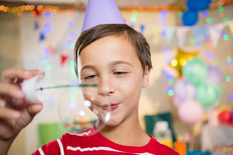Cute boy playing with bubble wand during birthday party. At home stock images