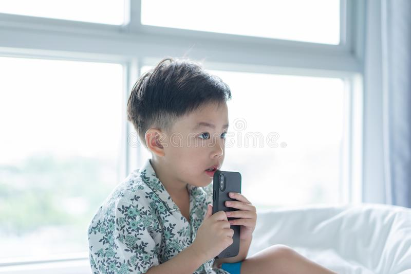 A boy is playing mobile phone in the morning on the bed stock images