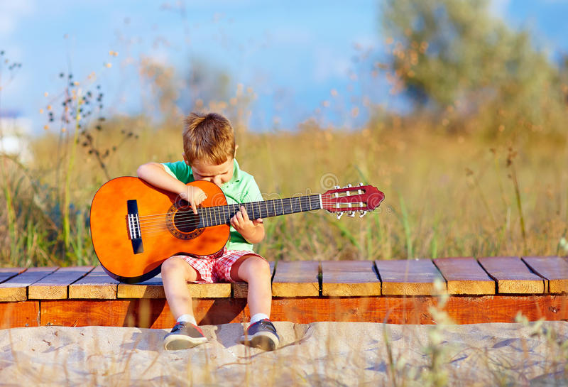 Cute boy playing a guitar on summer field stock images