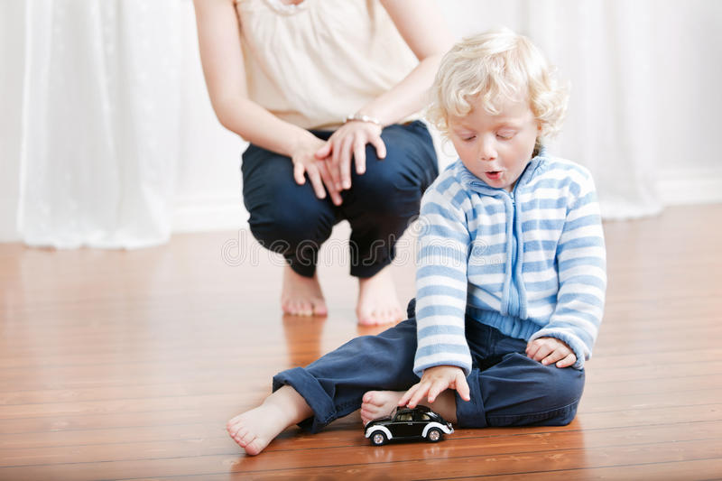Cute boy playing with toy car stock photography