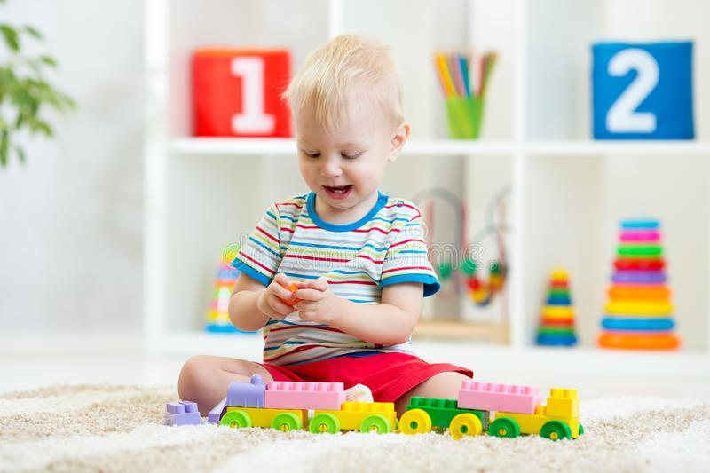 Cute boy plays with building blocks toys in nursery royalty free stock photos