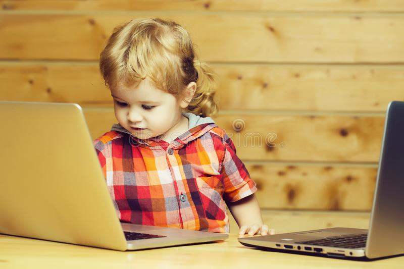 Cute boy plays on computers. Cute baby boy child with blond curly hair plays on two laptop computers on wooden background stock photo