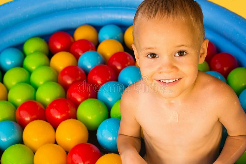 Cute boy in pool with colorful balls royalty free stock image