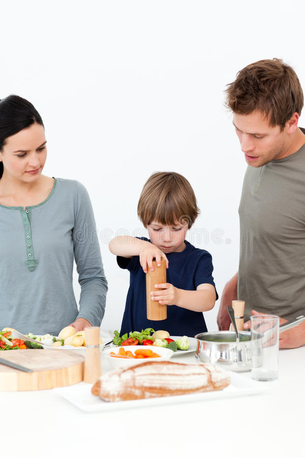 Cute Boy Putting Salt And Pepper In His Salad Stock Photos