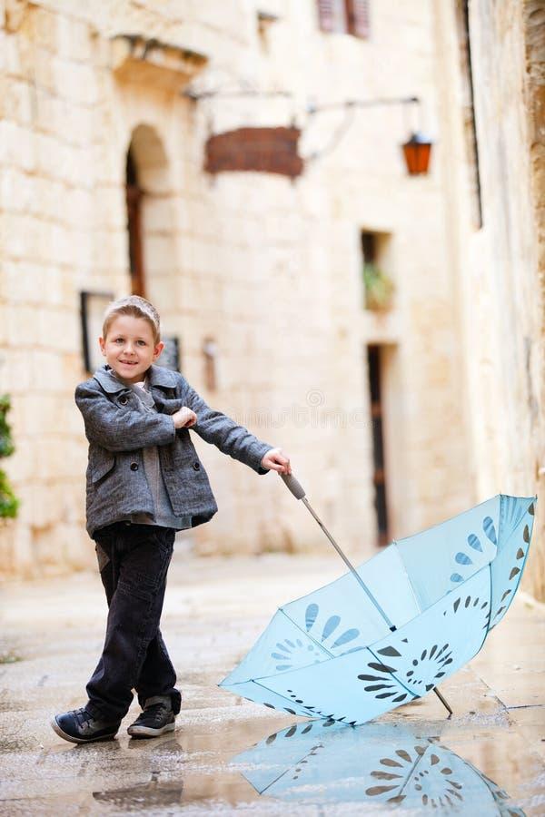 Cute boy on rainy day royalty free stock image