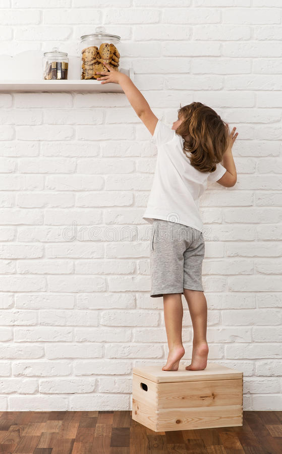 Cute boy reaching for the coockies royalty free stock photography