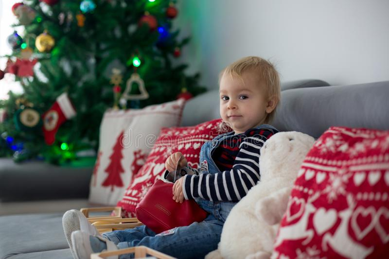 Cute boy, reading a book in front of Christmas tree at home stock image