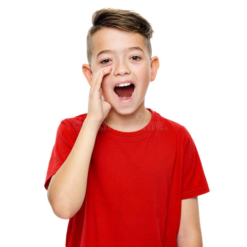 Cute boy in red T-shirt shouting. Speech therapy concept over white background. Front view. royalty free stock image