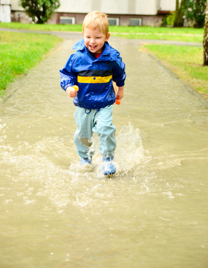 Cute boy running through puddle after the rain. Cute boy in special cloathes running through puddle after the rain stock photo