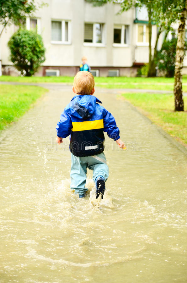 Cute boy running through puddle after the rain. Cute boy in special cloathes running through puddle after the rain stock photos