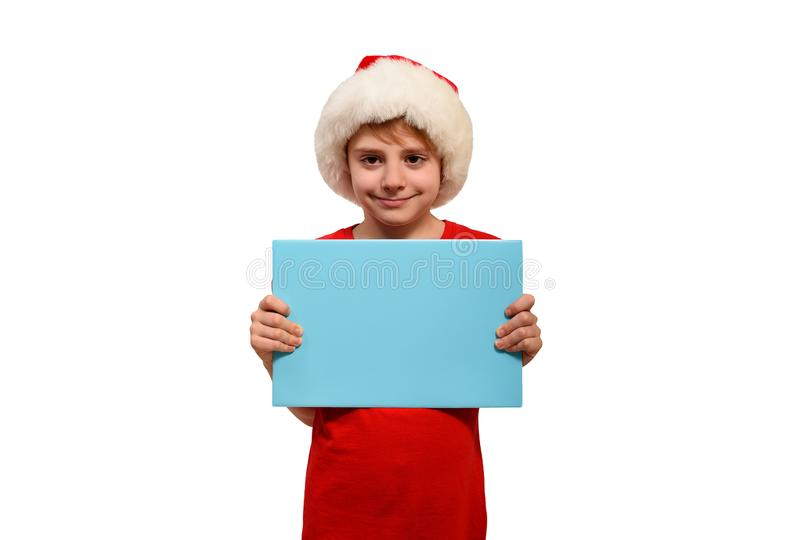 Cute boy in Santa hat with a blank blue board in his hands. Isolate on white stock photo