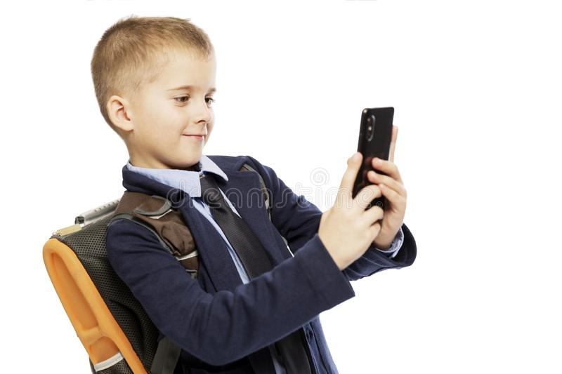 Cute boy with a school backpack looks into the phone, isolated on a white background royalty free stock photo