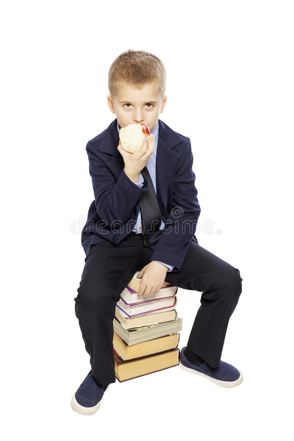 Cute boy in school uniform sits on books and eats an apple, isolated on white background. Vertical stock image