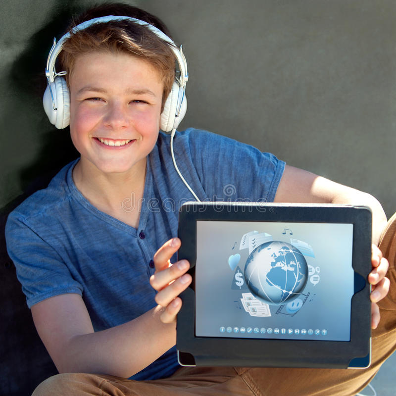 Cute boy showing tablet with multimedia symbols. stock photos