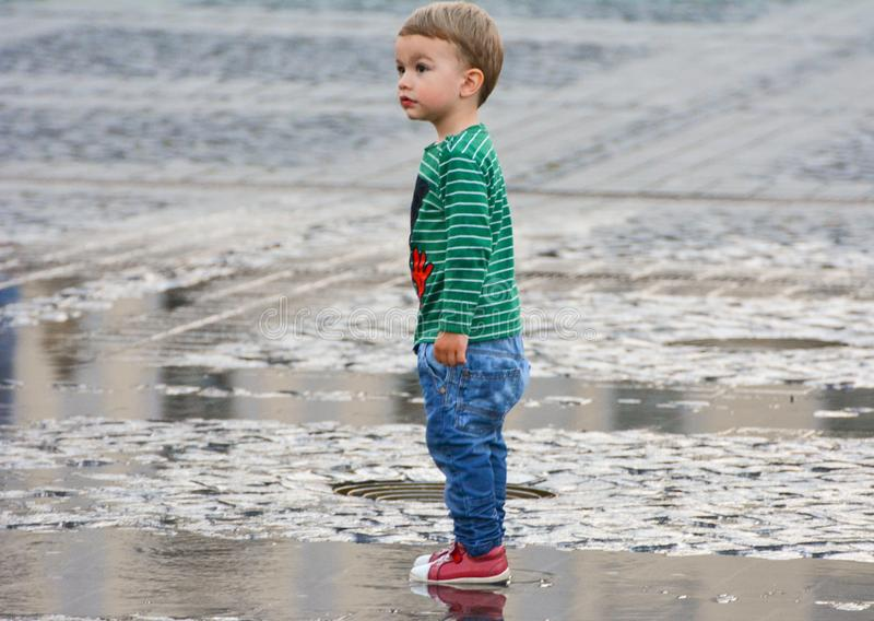 Cute boy. 06/03/2017-Sibiu, Romania. A cute, little boy playing in the puddle of water in the center of the town royalty free stock photos