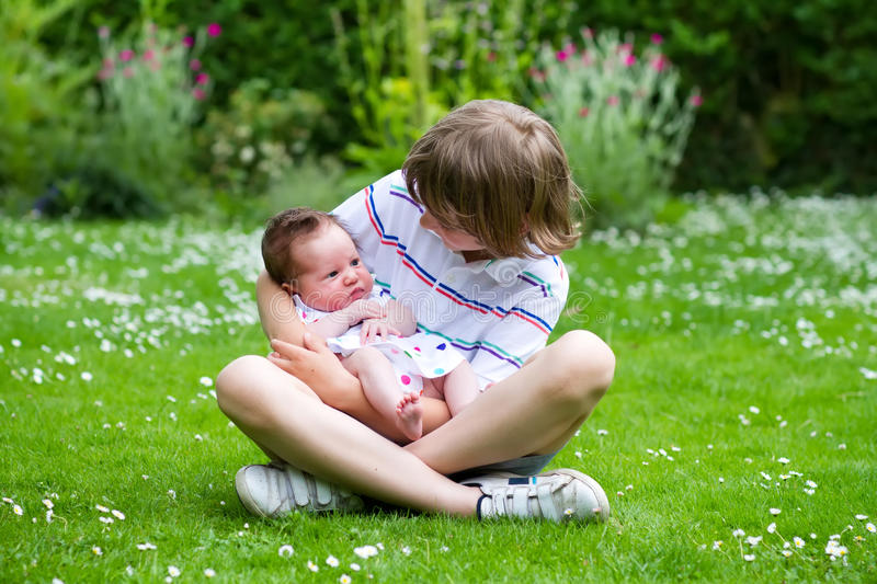 Cute boy sitting in a beautiful summer garden full with flowers holding his newborn sister royalty free stock image