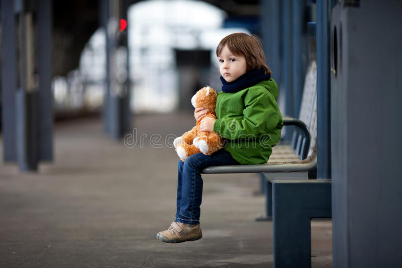 Cute boy, sitting on a bench with teddy bear, looking at a train royalty free stock image