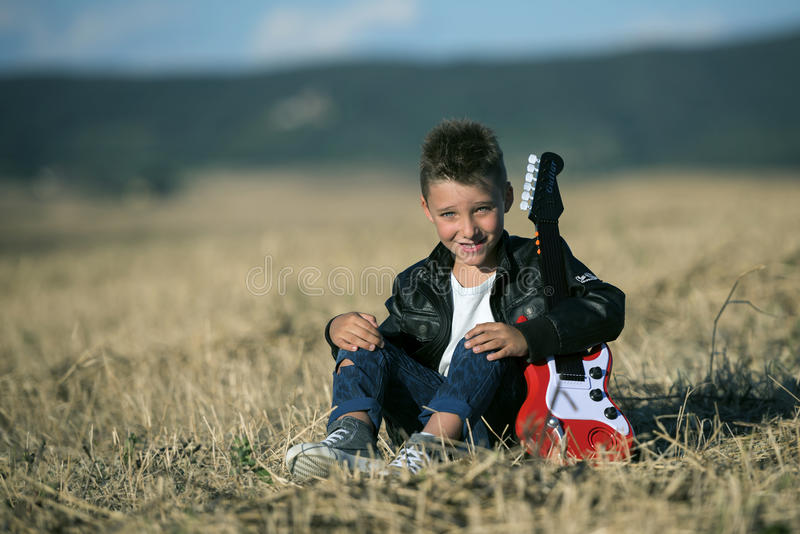 Cute boy sitting in the field with a guitar royalty free stock photography