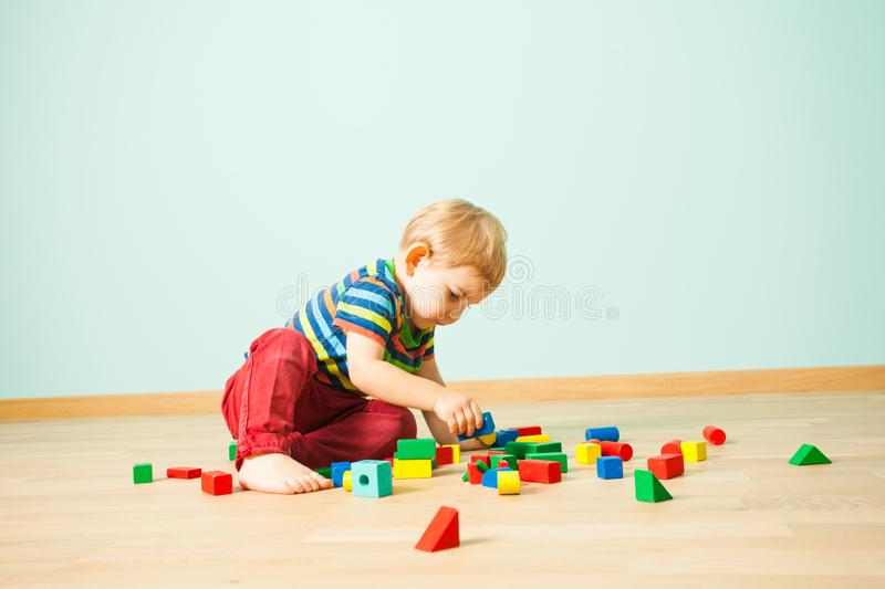 Cute boy sitting on a floor reconstructing smashed toy towers royalty free stock photography